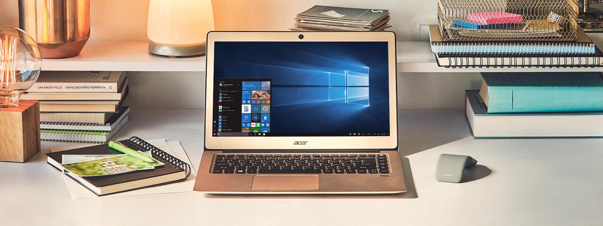 Bärbar Acer-dator och mus på ett skrivbord, omgivna av böcker och anteckningblock