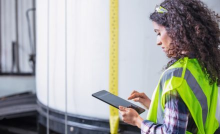 Image for: Female worker wearing neon vest and safety glasses using tablet. Industrial vats visible in background.