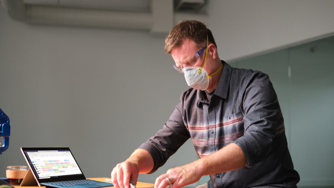 Manufacturing business owner wearing a mask and reviewing schedule in Shifts within Microsoft Teams.