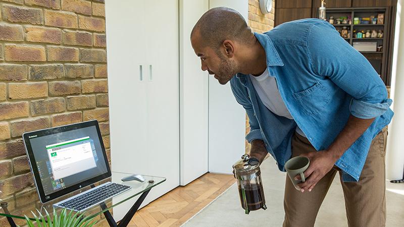 Người đàn ông nhìn vào màn hình máy tính để bàn đặt trên bàn kính, trong khi tay đang cầm cốc và một bình pha cà phê
