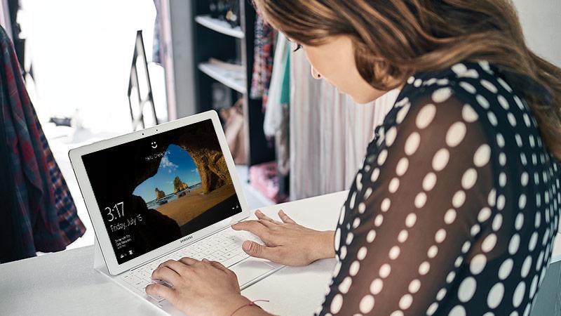 Người phụ nữ ngồi bên bàn làm việc đang nhập liệu vào máy tính bảng qua một bàn phím gắn kèm