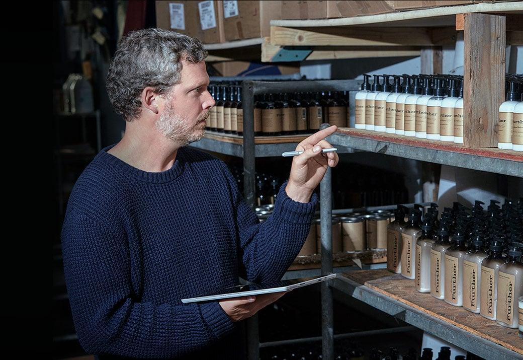 一位正在使用处于平板电脑模式的 Surface Pro 4 和触控笔盘点肥皂和洗涤剂库存的男士的图像。