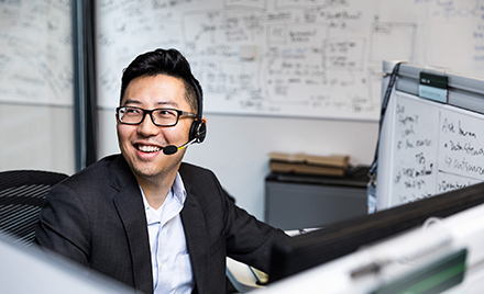 Image of a man wearing a headset and working at a computer.