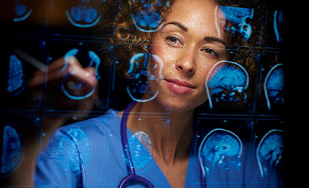Image of a neurosurgeon looking at scans on a computer screen.